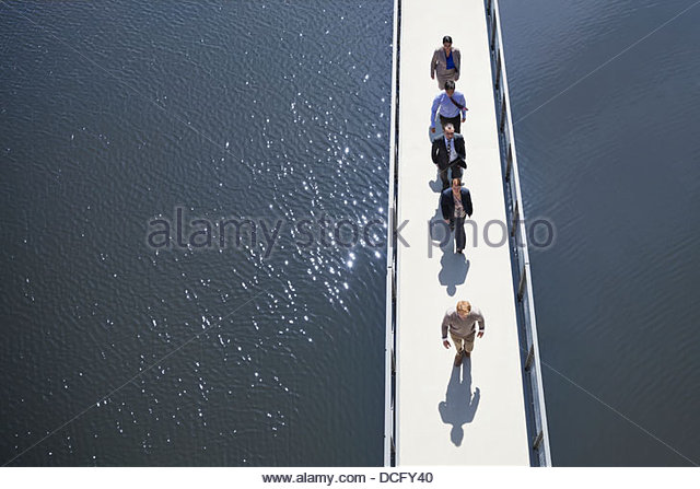 Business people walking in a row on a bridge - Stock Image
