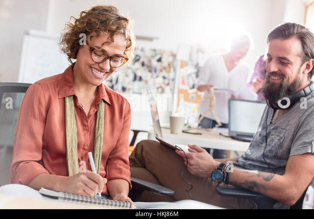 Smiling design professionals meeting and sketching in office - Stock Image