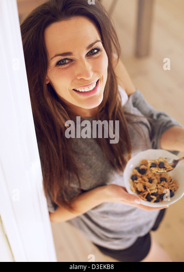 Charming woman looking up while eating her breakfast standing up - Stock Image