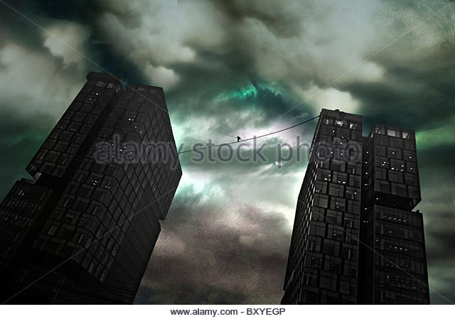 A figure walking a tight rope between two large office buildings under a stormy sky - Stock Image