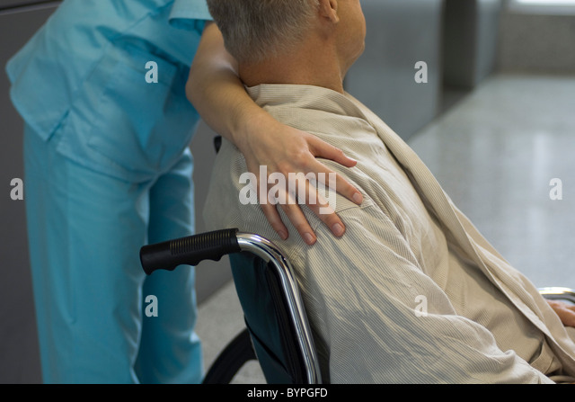 Nurse helping patient in wheelchair, cropped - Stock Image