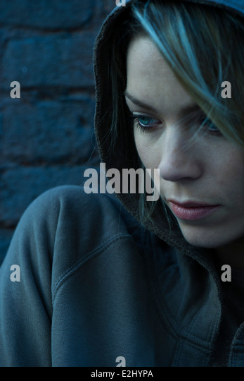 Woman in hooded sweatshirt pensively looking away - Stock Image