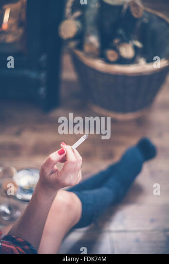 Woman sitting in front of wood burning stove smoking a cigarette - Stock Image