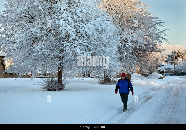Woman walking in the winter snow in the village of Slingsby in North Yorkshire in North East England - Stock Image