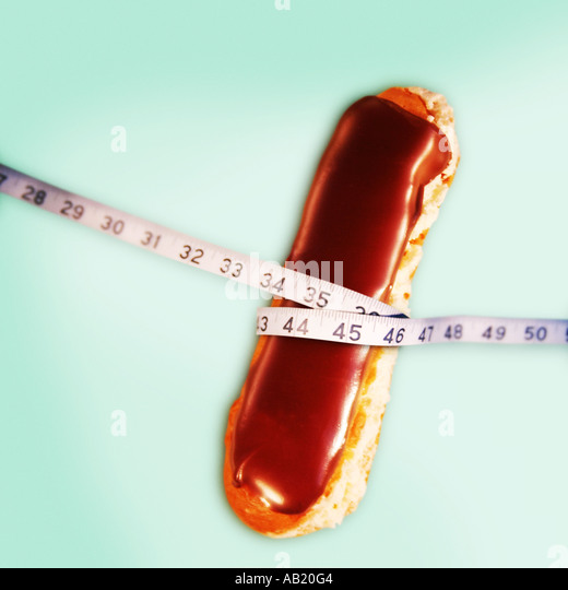 a chocolate eclair with a tape measure around the middle - Stock Image