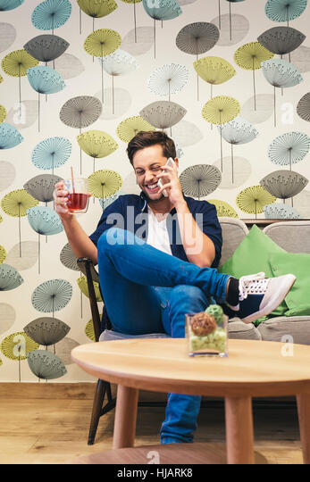 Bar smart casual young man talking on smartphone. Happy male adult speaking on mobile phone. - Stock Image