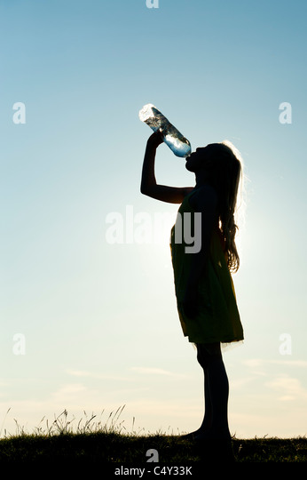 Girl drinking mineral water from plastic water bottle. Silhouette - Stock Image