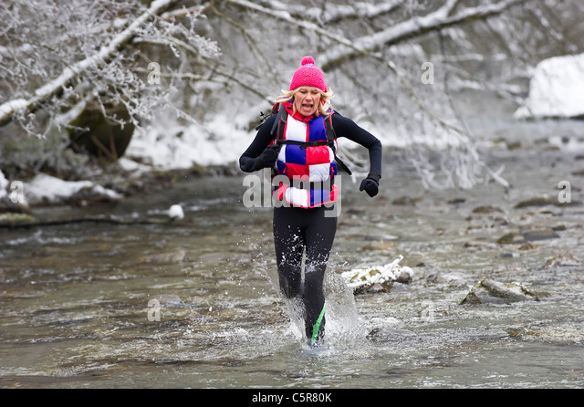 A jogger running through a snowy river bed and it's cold alpine waters. - Stock-Bilder