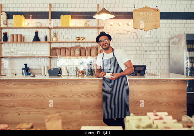 Portrait of happy young man wearing an apron and hat standing at a cafe counter holding a cup of coffee. Coffee - Stock-Bilder