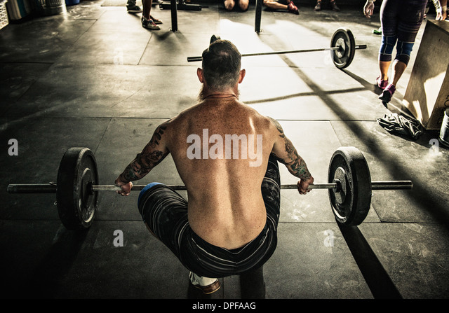 Mid adult man preparing to lift barbell in gymnasium - Stock Image