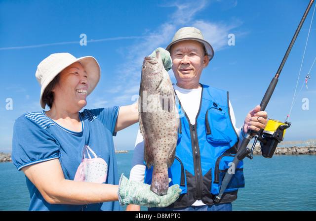 asian senior couple fishing and showing big grouper - Stock Image