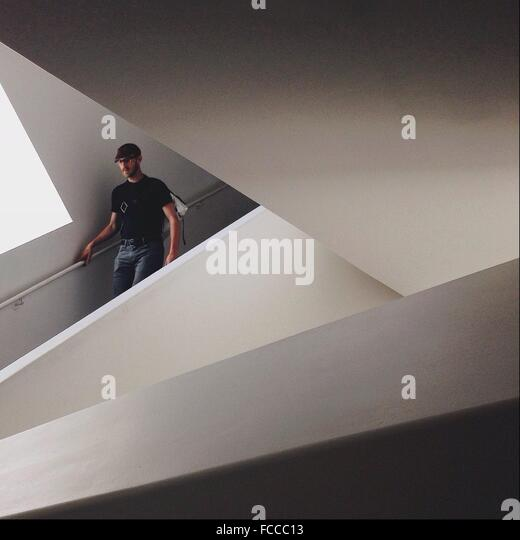 Man Walking Down On Stairs In Modern Building - Stock Image