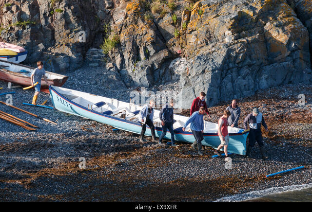 Gig racing - Carrying the gid boat down to the sea at Cadgwith Cove Cornwall - Stock Image