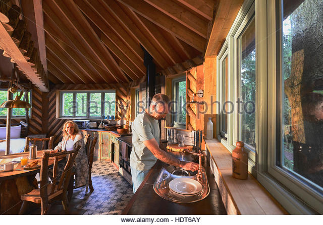 Mature man washing dishes after breakfast. - Stock Image