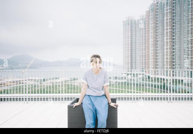 Thoughtful Woman Leaning By Chair Against Modern Buildings - Stock Image