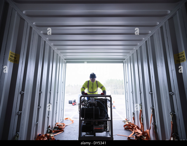 Emergency Response Team worker unloads equipment from shipping container - Stock Image