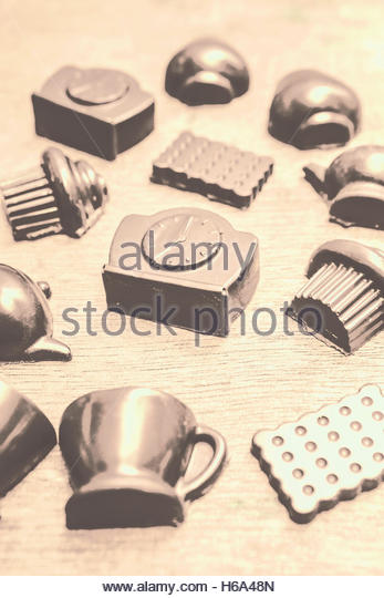 Retro chocolate decorations with a group of solid choc tea cups, clocks, and food snacks. Antique tea party concept - Stock Image