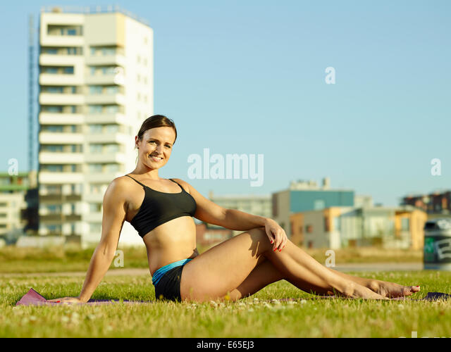 Sporty fitness woman in the park early in the morning, urban background - Stock Image