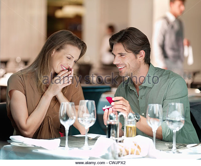 Man with engagement ring proposing to woman in restaurant - Stock Image