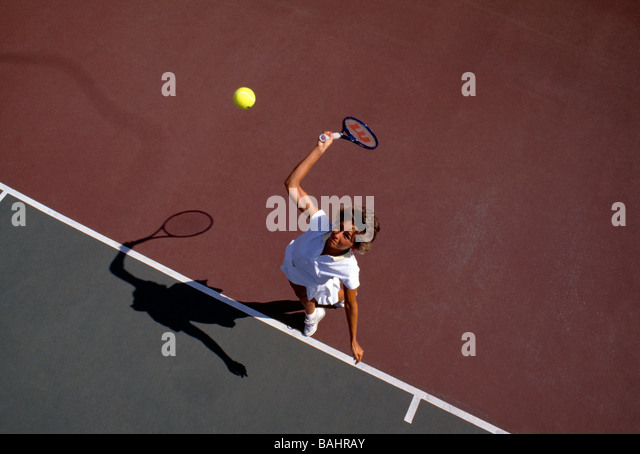 Overhead view of female tennis player hitting the ball with a racket - Stock Image
