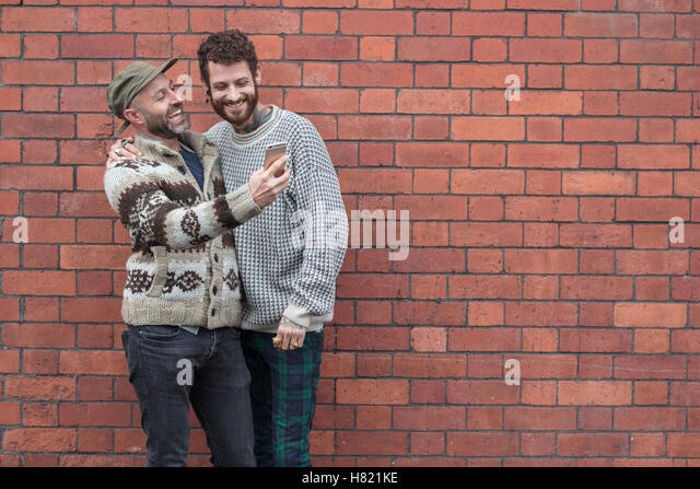 Gay couple lent against a wall, sharing content on a phone - Stock Image