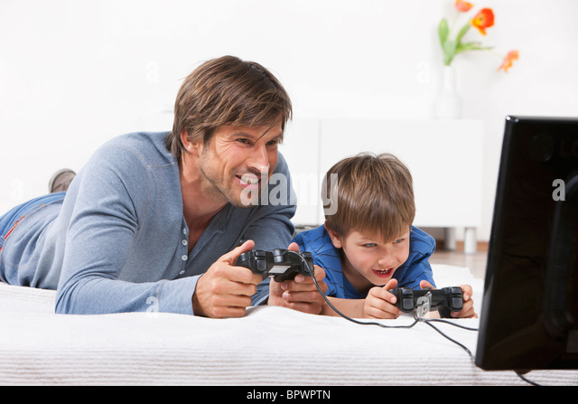Father and son playing a video game - Stock Image