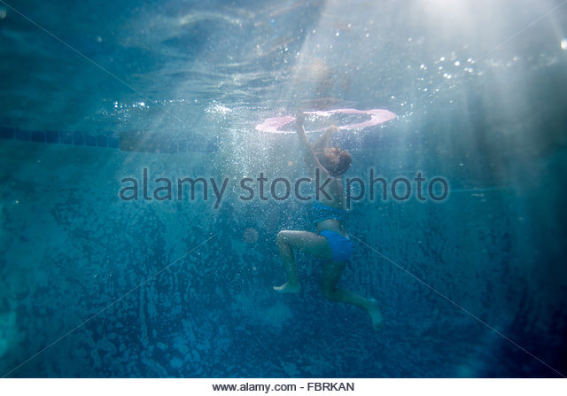 Girl playing in a pool on a warm September day in San Clemente, California. - Stock Image