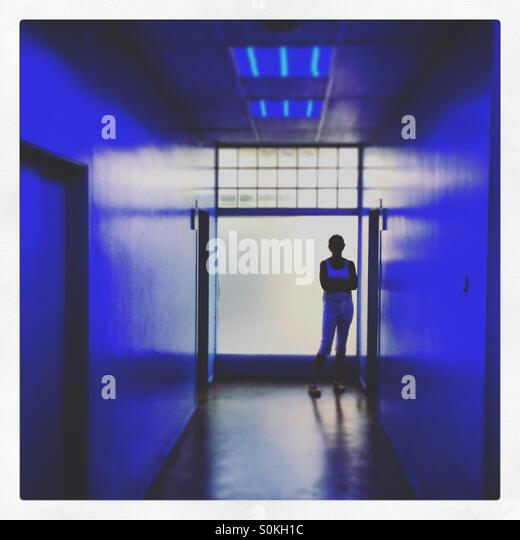 A silhouette of a female at the end of a blue corridor - Stock Image
