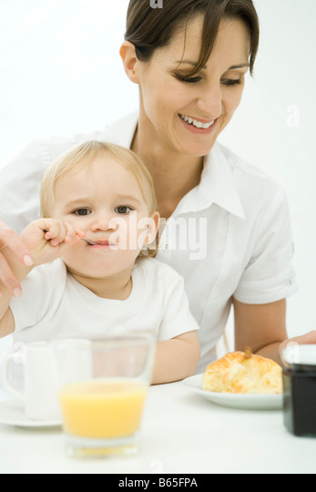 Professional woman sitting at breakfast table, toddler sitting on lap, spoon in mouth - Stock-Bilder