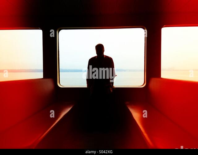 Silhouette of a man in the window of a ferry boat in Puget Sound - Stock-Bilder