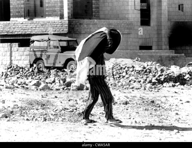 Arab-Israeli War, Jordanian in pajamas (carrying mattress & blankets) walking through war-torn city of Amman, - Stock Image
