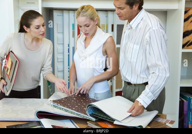 Woman assisting couple choosing wallpaper samples in store - Stock Image