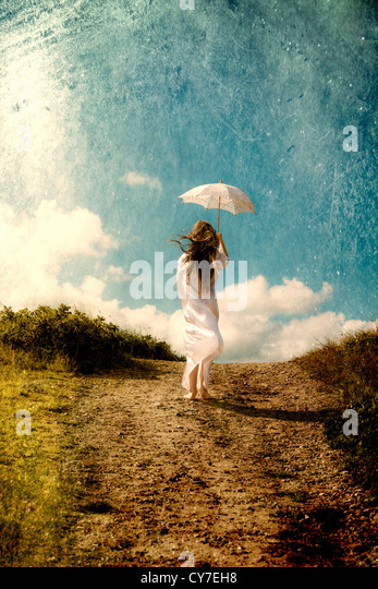 a girl in a white dress is walking in the dunes with a parasol - Stock Image