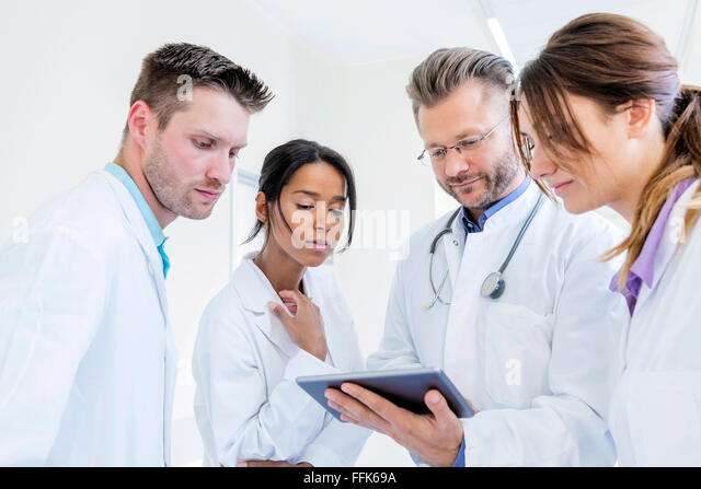 Doctor and coworkers using digital tablet in hospital - Stock Image