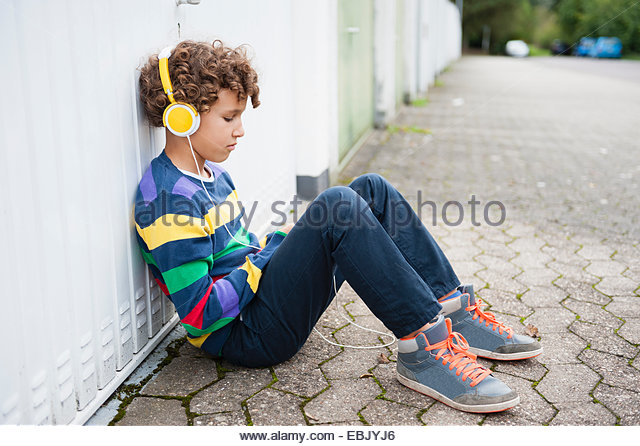 Sullen boy sitting leaning against wall listening to headphones - Stock Image
