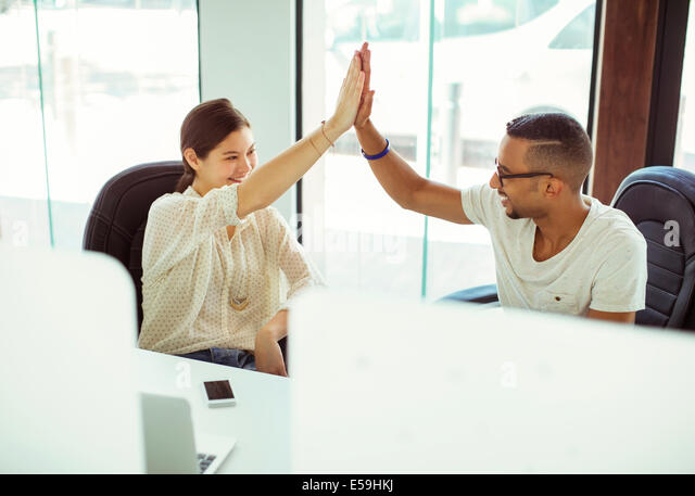 People high fiving in office - Stock Image