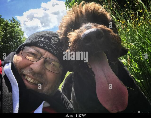 Man taking a selfie with his pet dog - Stock Image