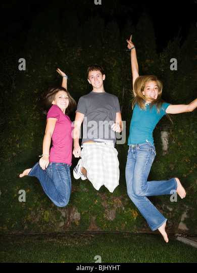 teenagers in a backyard at night - Stock Image