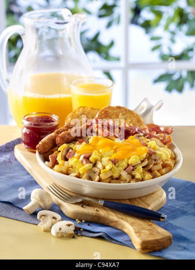 Scrambled egg and ham skillet breakfast served with sausage, bacon, toast and orange juice - Stock Image