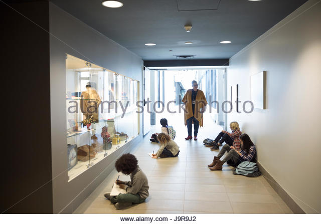 Docent watching students taking notes on floor at exhibit on field trip in war museum - Stock-Bilder