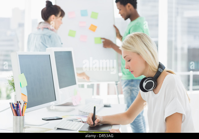Artist drawing something on graphic tablet with colleagues behind at office - Stock Image