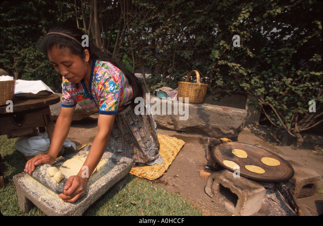 Guatemala La Antigua colonial capitol until earthquake making Mayan style tortillas with stone roller & table - Stock Image