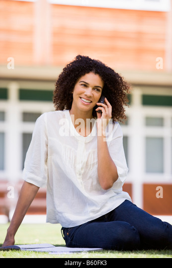 Woman on lawn of school using cellular phone - Stock Image