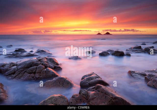 An amazing sunset paints the sky with glorious colours as the silky smooth sea laps around the rocks at Porth Nanven. - Stock-Bilder