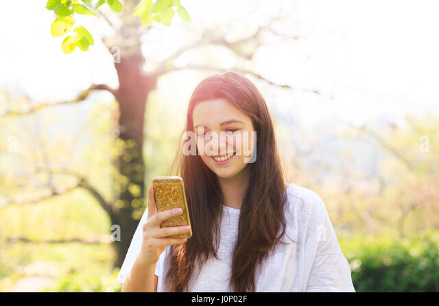 Smiling teenage girl with cell phone - Stock Image