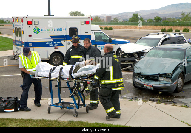 Paramedics and firefighters respond to an automobile injury accident in Boise, Idaho, USA. - Stock Image