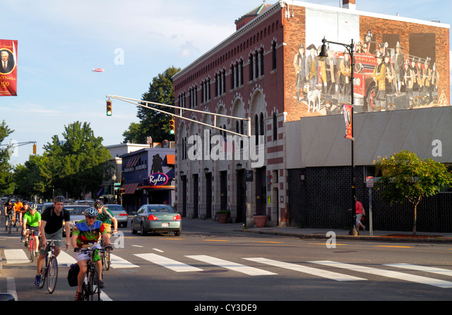 Massachusetts Boston Cambridge Inman Square Hampshire Street bikers cyclists historic fire department house traffic - Stock Image