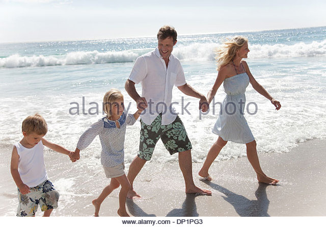Family wading in ocean - Stock Image
