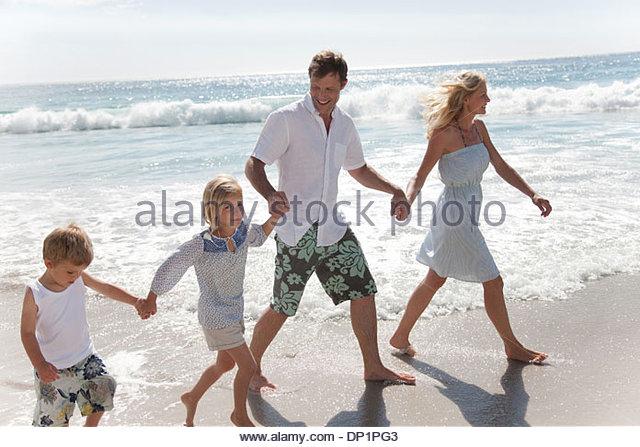 Family wading in ocean - Stock-Bilder