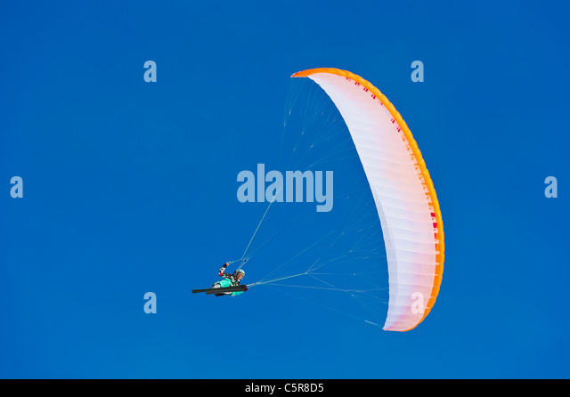 A Paraglider pilot smiles as makes makes a fast banked turn. - Stock-Bilder